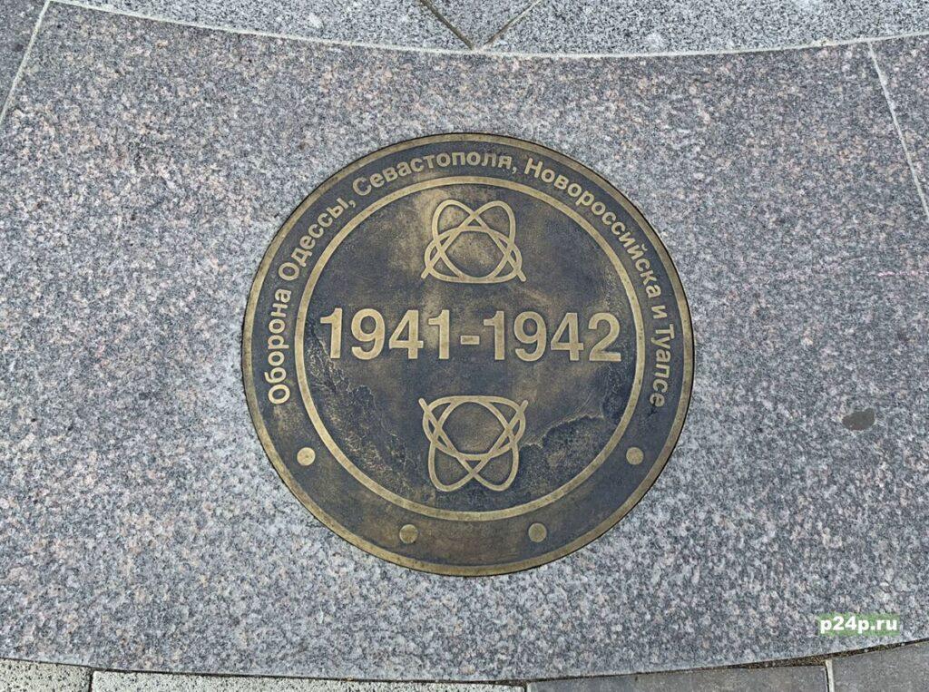 Железные знаки в плитке на Аллее героев